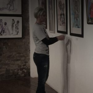 Barri's picture in menier gallery, she is standing in front of her two angles paintings
